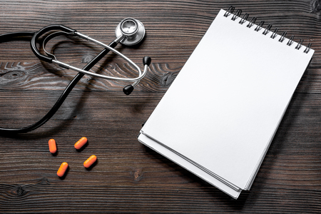 Notebook, phonendoscope and pills on dark wooden desk top view call a doctor. Reklamní fotografie