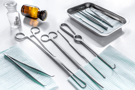 Rejuvenation by plastic surgery: medical instruments on white table backgrond
