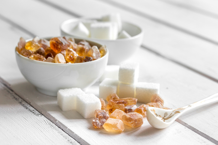 variety of sugar in bowls on white wooden table background Stock Photo