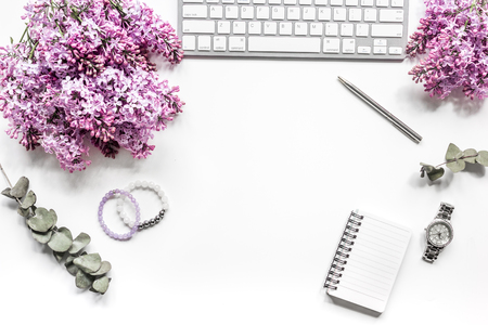 woman home office with lilic flowers, notebook white desk background top view mock up Stock fotó