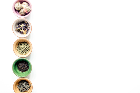 teaparty: herbs in colorful bowls to make tea on white table background top view mock-up