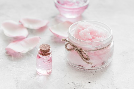 woman in bath: homemade spa with rose cosmetic set, cream, salt and oil on white background