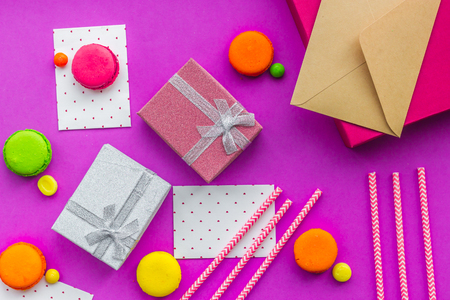 Birthday greeting cards and wrapped gifts on fuchsia background top view.