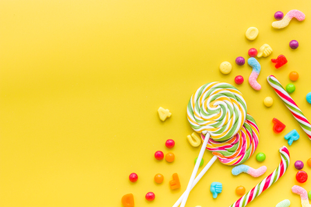 Sweets for birthday including lollipop and drops on yellow background top view copyspace. Stok Fotoğraf