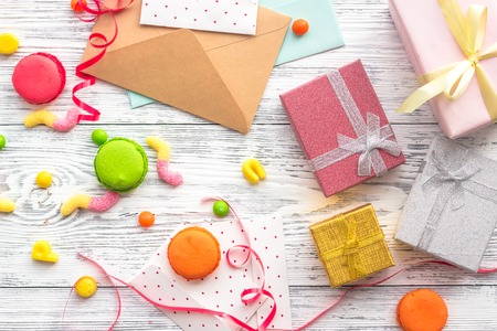 Birthday concept with wrapped gifts, greeting cards and sweets on grey wooden background top view.