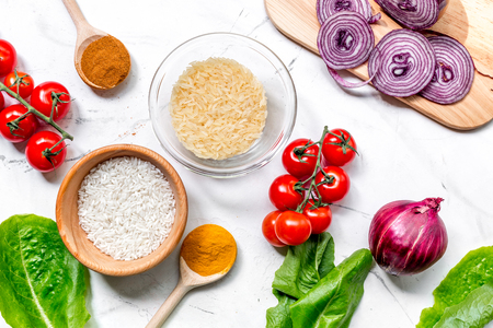 Cooking paella with vegetables and rice ingredients on white kitchen desk background top view