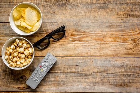 TV remote control, snacks, beer for whatchig film on wooden desk background top view space for text Archivio Fotografico