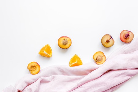 Orange and peach summer sweet dessert on fabric white desk background top view mock-up Stock Photo