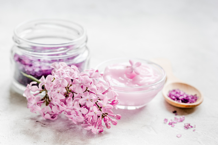 woman in bath: take bath with lilac cosmetic spa set and blossom on stone table background Stock Photo