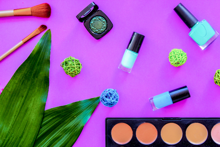 decorative cosmetics design with eye shadow, nail polish and make-up brushes on purple table background top view pattern Stock Photo