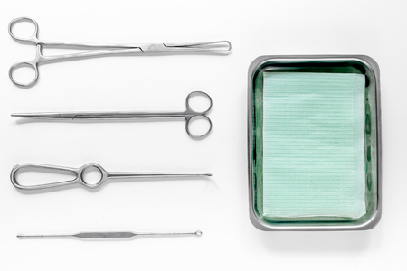 surgical instruments and tools including scalpels, forceps and tweezers on white table top view. Stock Photo