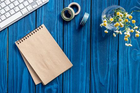 自宅の花、ノート テキストの青い木製の背景トップ ビュー空間上のキーボードとの夏オフィスの机 写真素材