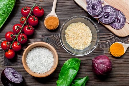 homemade paella ingredients composition with rice, tomato, onion on wooden kitchen table background top view Stock Photo