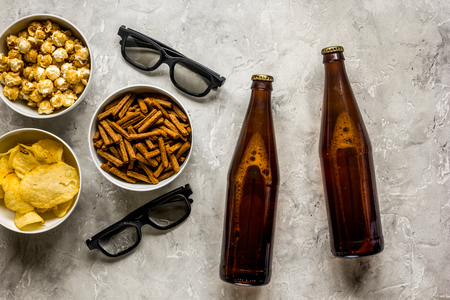 Soirée de fabrication de films avec de la bière, des miettes, des chips et du maïs soufflé sur fond de pierre vue de dessus Banque d'images - 80316322