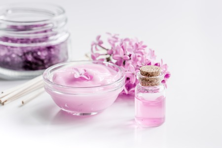 homemade organic salt, cream, extract in lilac cosmetic set with flowers on white table background