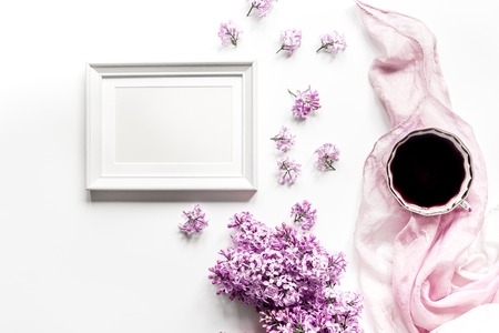 Spring lilac flowers on workdesk at female home office with frame and coffee white background top view mockup