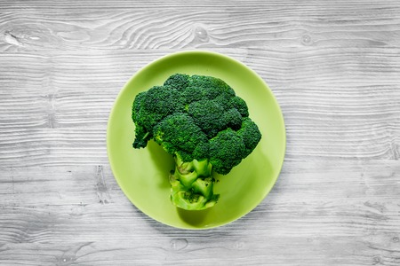 healthy food with green vegetables, fruits for fitness dinner on gray table background top view