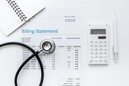 Déclaration de facturation des soins de santé avec le stéthoscope du médecin sur la table blanche arrière-plan top view maquette