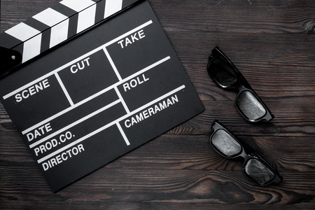 screenwriter: Attributes of film director. Movie clapperboard and sunglasses on wooden table background top view Stock Photo