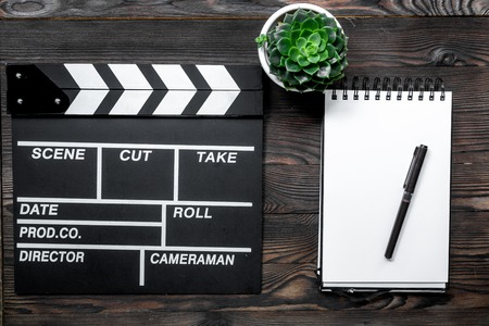 screenwriter: Work table of producer. Movie clapperboard and notebook on wooden table background top view Stock Photo