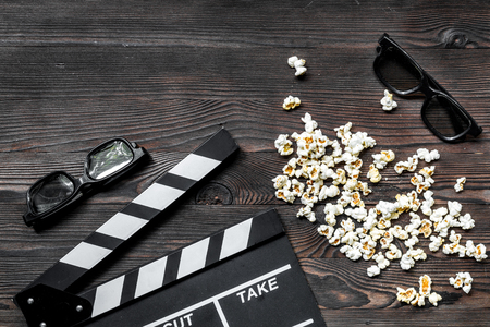 Watching the film. Movie clapperboard, sunglasses and popcorn on wooden table background top view copyspace Stock Photo