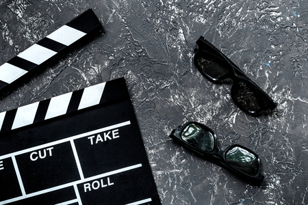 Attributes of film director. Movie clapperboard and sunglasses on grey stone table background top view