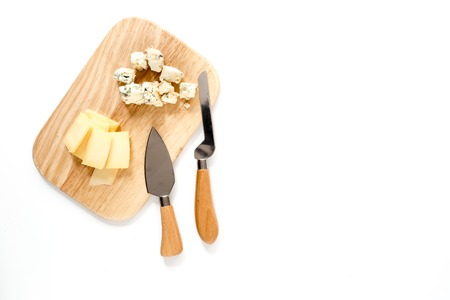 Aperitive parmesan cheese and cheese with blue mould on a cutting board on white background top view space for text