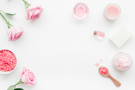 rose organic cosmetics with salt, cream and oil on white table background top view