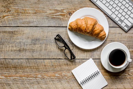 coffee and croissant for breakfast of businessman wooden office desk background top view space for text