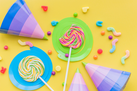 Lollipops and party hats for happy birthday on yellow background top view.