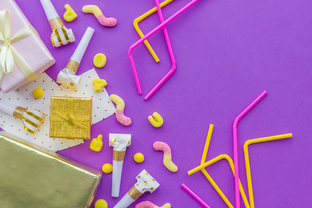 Birthday concept with gifts, greeting cards and party whistles on violet background top view copyspace. Stock Photo