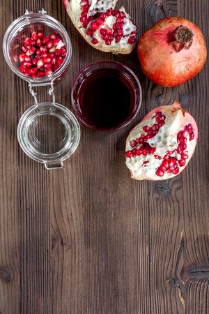 squeezing: red pomegranate juice and sliced fruit on dark wooden background top view mockup