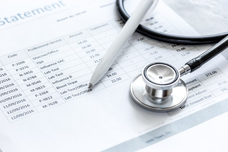 billing statement for for medical service in doctor's office on stone desk background
