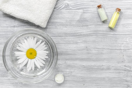chamomile flower: hands care set for manicure with chamomile on gray wooden background top view space for text. Stock Photo
