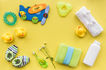 Baby accessories for bath with body cosmetic and toy ducks on yellow background top view mock-up Stock Photo