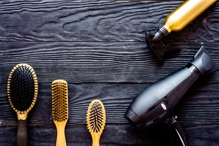 Brushes, hairdryer and hairspray on grey wooden background top view.