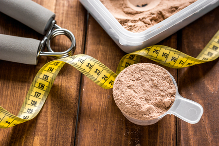 Sport diet nutrition and fitness equipment , bars and measure tape on wooden background Archivio Fotografico