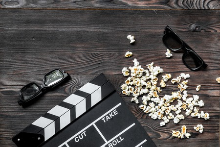 Watching the film. Movie clapperboard, sunglasses and popcorn on wooden table background top view copyspace.