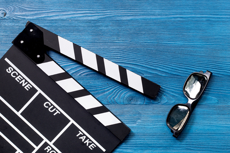 Attributes of film director. Movie clapperboard and sunglasses on blue wooden table background top view.
