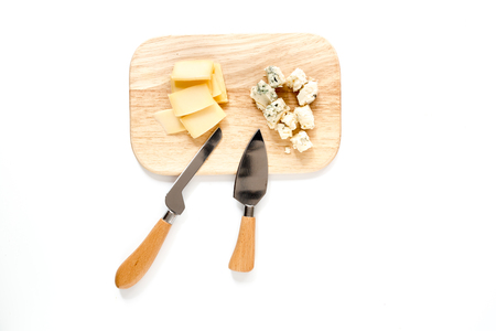 Aperitive parmesan cheese and cheese with blue mould on a cutting board on white background top view