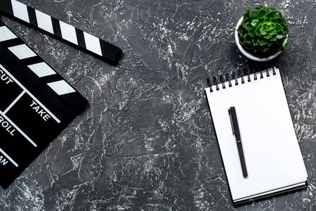 プロデューサーの作業テーブル。映画カチンコと灰色の石の背景上のノートブックを表示 copyspace 写真素材