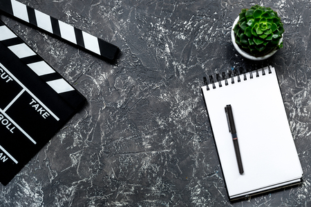 Work table of producer. Movie clapperboard and notebook on grey stone background top view copyspace