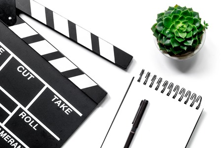Work table of producer. Movie clapperboard and notebook on white background top view Banco de Imagens