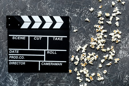Watching the film. Movie clapperboard and popcorn on grey stone table background top view