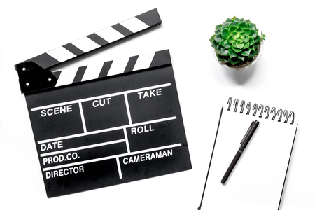 Work table of producer. Movie clapperboard and notebook on white background top view Stock Photo