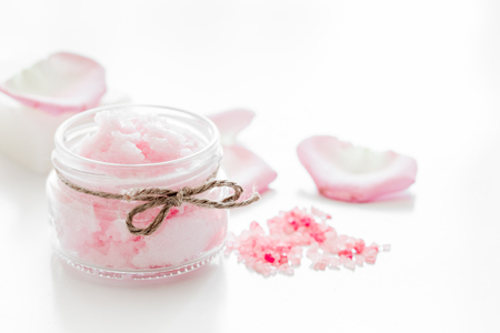 woman in bath: body treatment with rose petals and cosmetic set white desk background