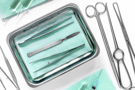 Surgical instruments and tools including scalpels, forceps and tweezers on white table top view Stock Photo