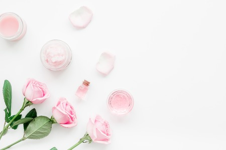 cosmetic set with rose blossom and body cream on white desk background top view mock-up Standard-Bild