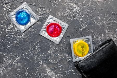 mannelijke anticonceptie voor veilig vrijen met condooms in portefeuille op donkere achtergrond bovenaanzicht