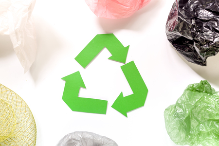 Paper recycle sign with plastic garbage on white background top view